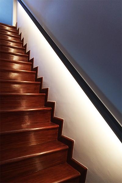 Scala in legno su misura illuminata dal corrimano